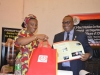 Mrs. Nnenna Akajemeli presenting SERVICOM materials to Dr. Elvis Oglafa, Secretary to the Commission