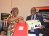 Mrs. Nnenna Akajemeli presenting SERVICOM materials to Dr. Elvis Oglafa, Secretary to the Commission