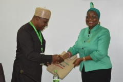 Spokesperson for the Commission, Mrs. Rasheedat Okoduwa, presenting IEC materials to Dr. F. Adeyemi
