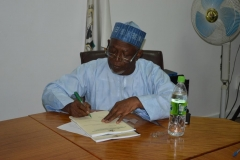 Alhaji Bako Abdullahi signing handover documents during the ceremony