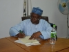 Alhaji Bako Abdullahi signing handover documents during the ceremony.