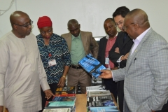 Dr. Elvis Oglafa, Secretary to the Commission, taking a closer look at some of the books presented to ICPC's Academy by UNODC