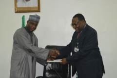 ICPC Acting Chairman, Dr. Musa Usman Abubakar receving some materials from the Executive Secretary NSC, Mr. Hassan Bello during the courtesy visit
