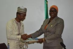 Spokesperson for the Commission, Mrs. Rasheedat Okoduwa [R] presenting some IEC materials to Mr. Hamza Lawan [L]
