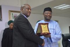 Acting Chairman ICPC, Dr. Musa Usman Abubakar receiving a plaque from the INEC Chairman, Prof. Mahmoud Yakubu